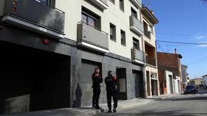 Dos mossos custodian la entrada en un domicilio de Vic, este miércoles por la mañana.