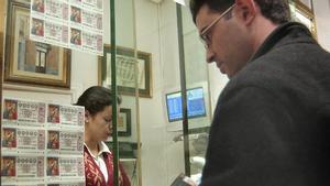Persona comprando lotería en una administración.