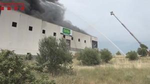 Bomberos trabajan en la extinción de un incendio en una fábrica de Barcelona.