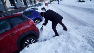 Una persona quita nieve para poder sacar el coche e ir a trabajar.