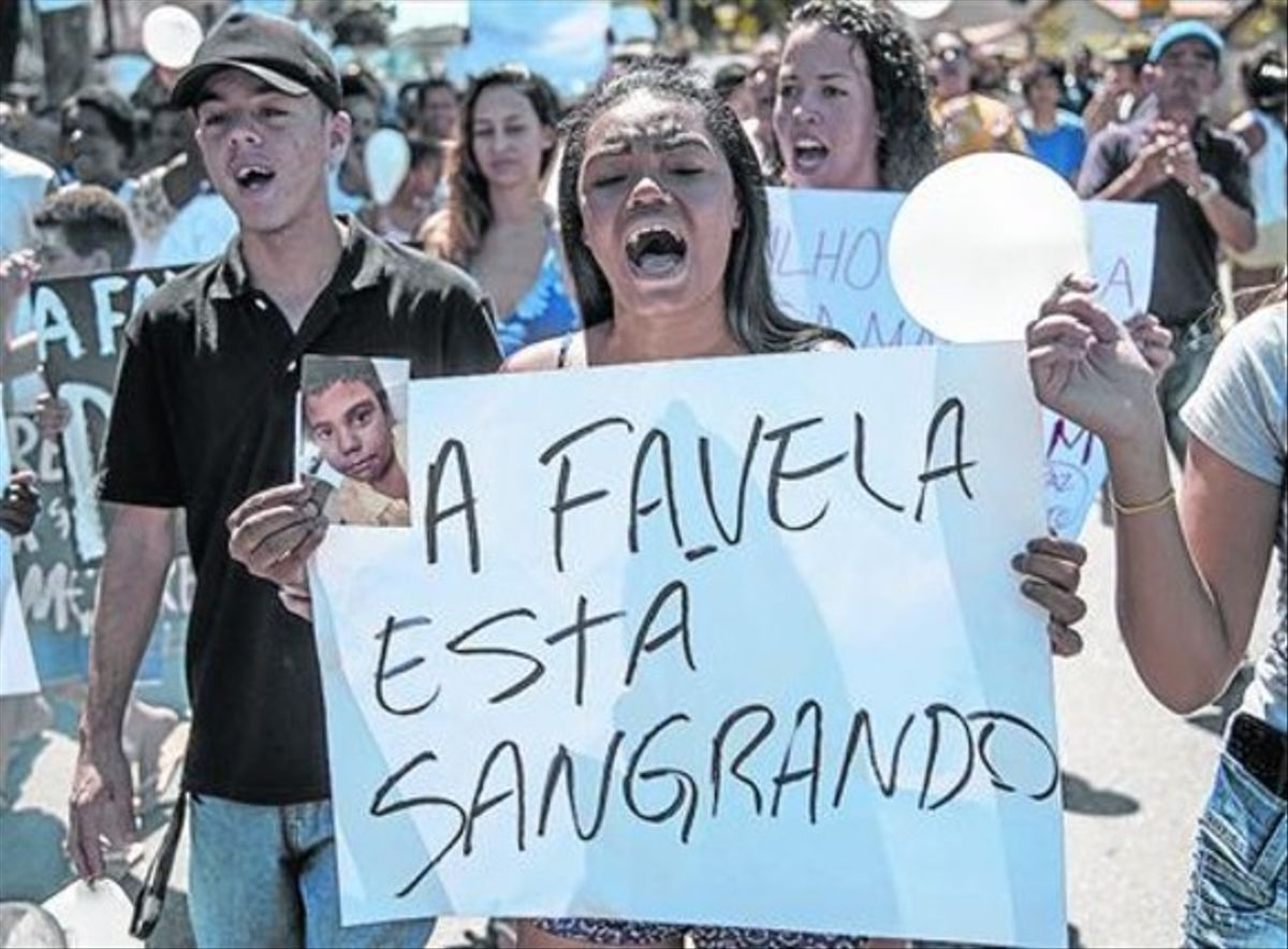 Una dona participa en la 'marxa per la pau' a la favela Alemao després de la mort d'un nen per la policia.