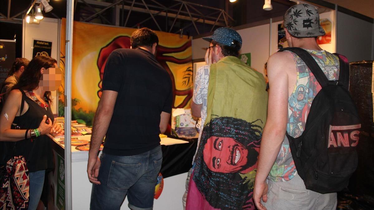 Varios jóvenes se acercan a pedir información al estand de Energy Control instalado en un festival de verano.
