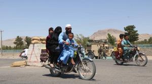 Una familia afgana pasa fente a las fuerzas de seguridad en una de las entradas de Herat.