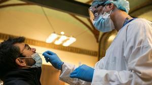 Un hombre se somete a un test de coronavirus durante la realización de cribajes masivos en Barcelona.