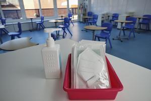 Mascarillas KN-95 y gel desinfectante en la mesa del profesor de un aula de Madrid.