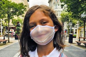 Una niña con un modelo de mascarilla higiénicas transparente reutilizable Biovest Expression.