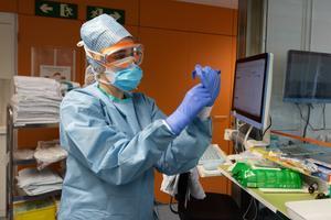 Personal sanitario del Hospital Clínic se preotege con guantes, mascarilla, gafas, bata y gorro.