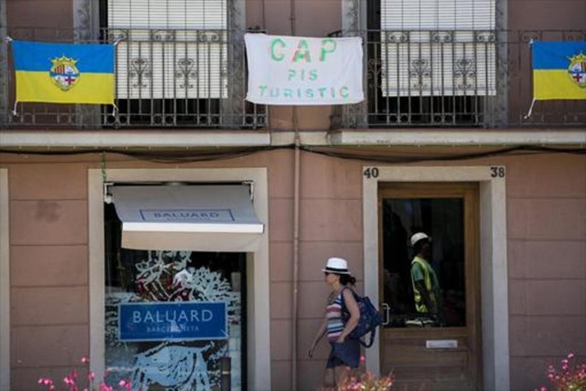 Cartel contra los pisos turísticos en la Barceloneta, uno de los barrios de Barcelona con más apartamentos en alquiler.