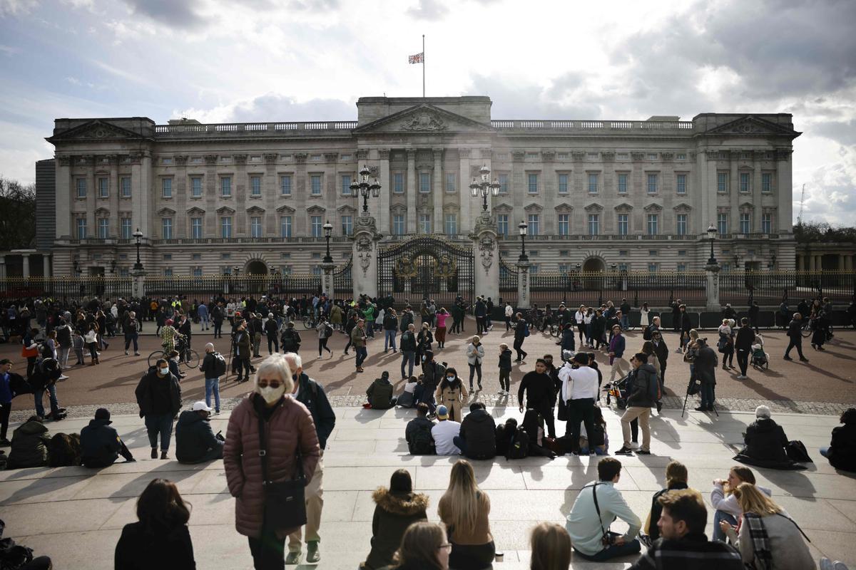 Decenas de ciudadanos frente a las puertas del palacio de Buckingham, donde ondea la bandera a media asta por la muerte del duque de Edimburgo.