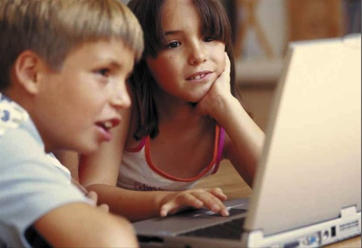 Niños navegando por internet ante un portátil.