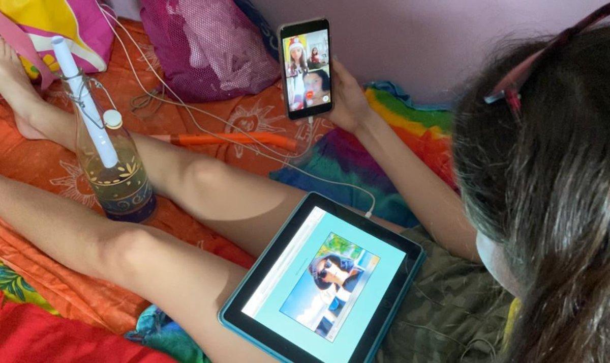 Una niña está conectada con sus amigas para resolver juntaslos enigmas.