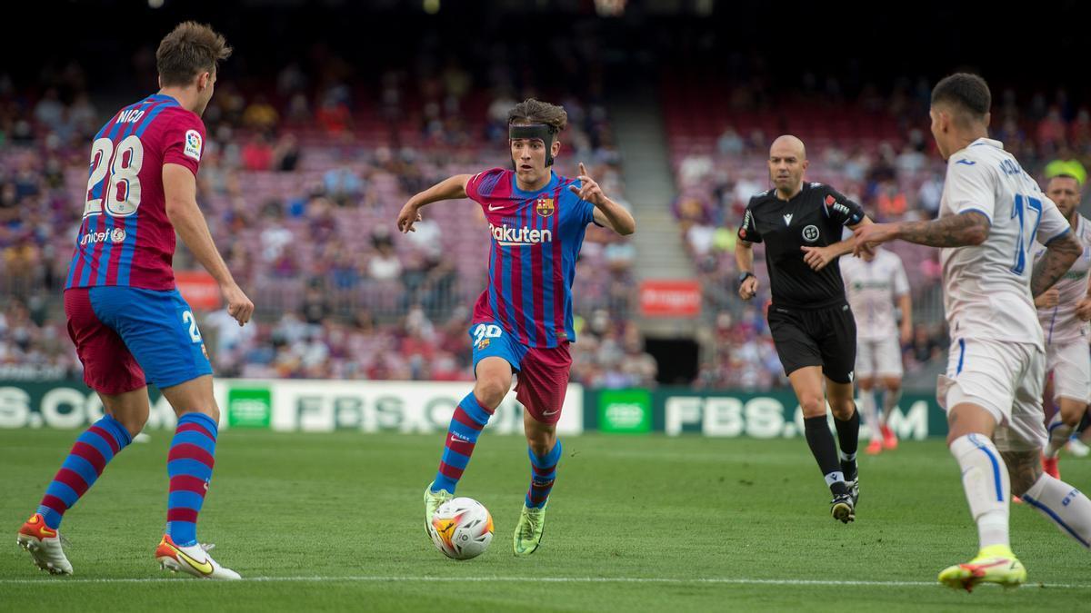 Gavi conduce el balón entre la defensa del Getafe con Nico observándole.