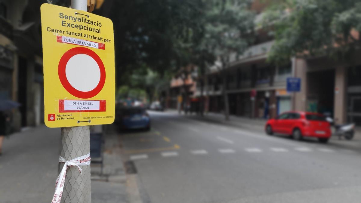 La calle de Viladomat, con un cartel provisional de tráfico en el que se anuncia la Cursa de la Mercè.