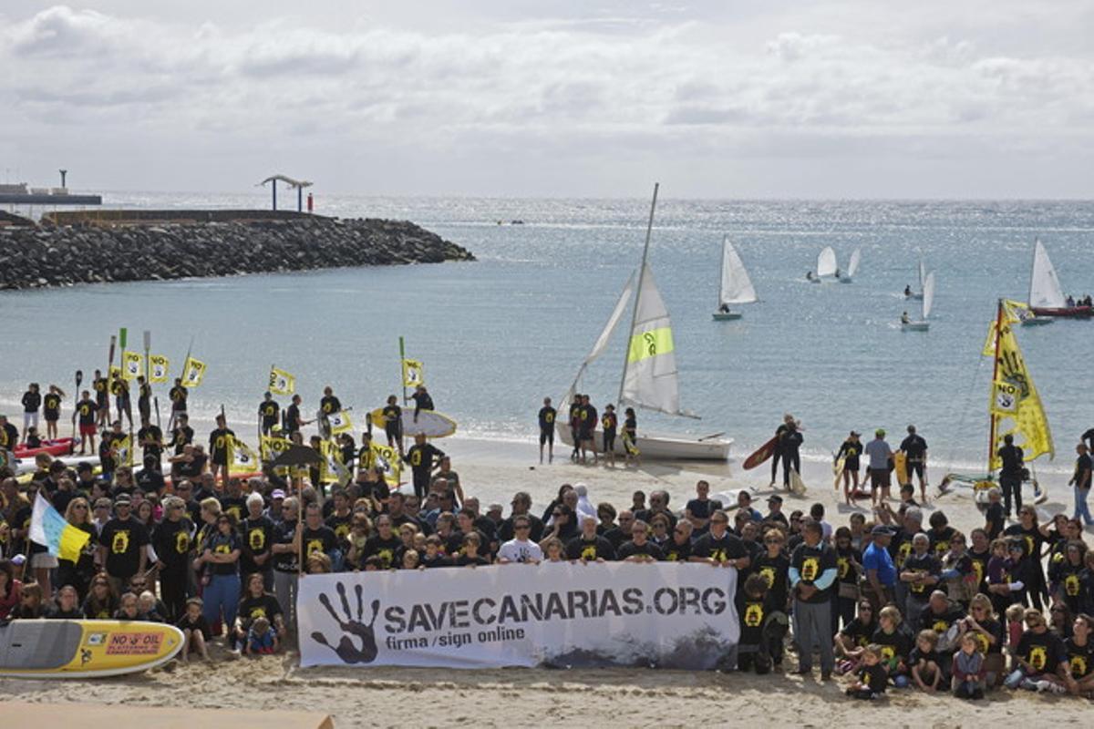 GRA223. PUERTO DE ROSARIO (FUERTEVENTURA), 22/03/2014.- Unas 300 personas se han concentrado hoy en la zona de Playa Chica, en Puerto del Rosario (Fuerteventura), y se han subido a tablas de surf y piraguas, o se han puesto trajes de baño y camisetas para expresar su rechazo al petróleo, dentro de la convocatoria de los colectivos Agonane Ben Magec, Clean Ocean Project y Savecanarias.org en contra del proyecto de prospecciones petrolíferas en aguas canarias. EFE/Carlos De Saa