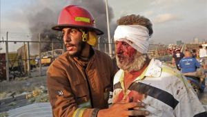 Un hombre herido es ayudado por un bombero, tras la explosión en el puerto de Beirut.