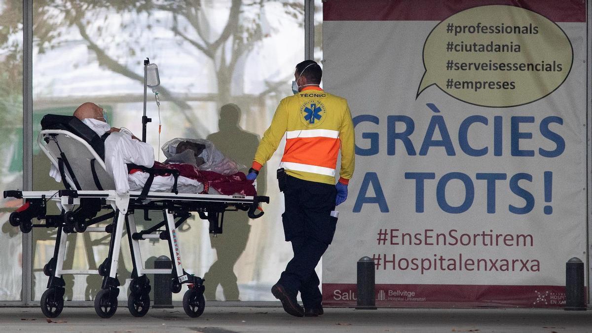 Un técnico de ambulancia del SEM traslada a un enfermo en la entrada a urgencias del Hospital de Bellvitge, el 3 de noviembre.