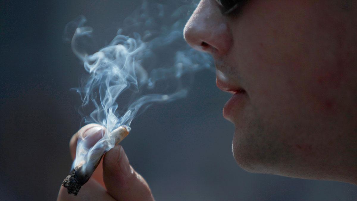 Un joven fuma marihuana.