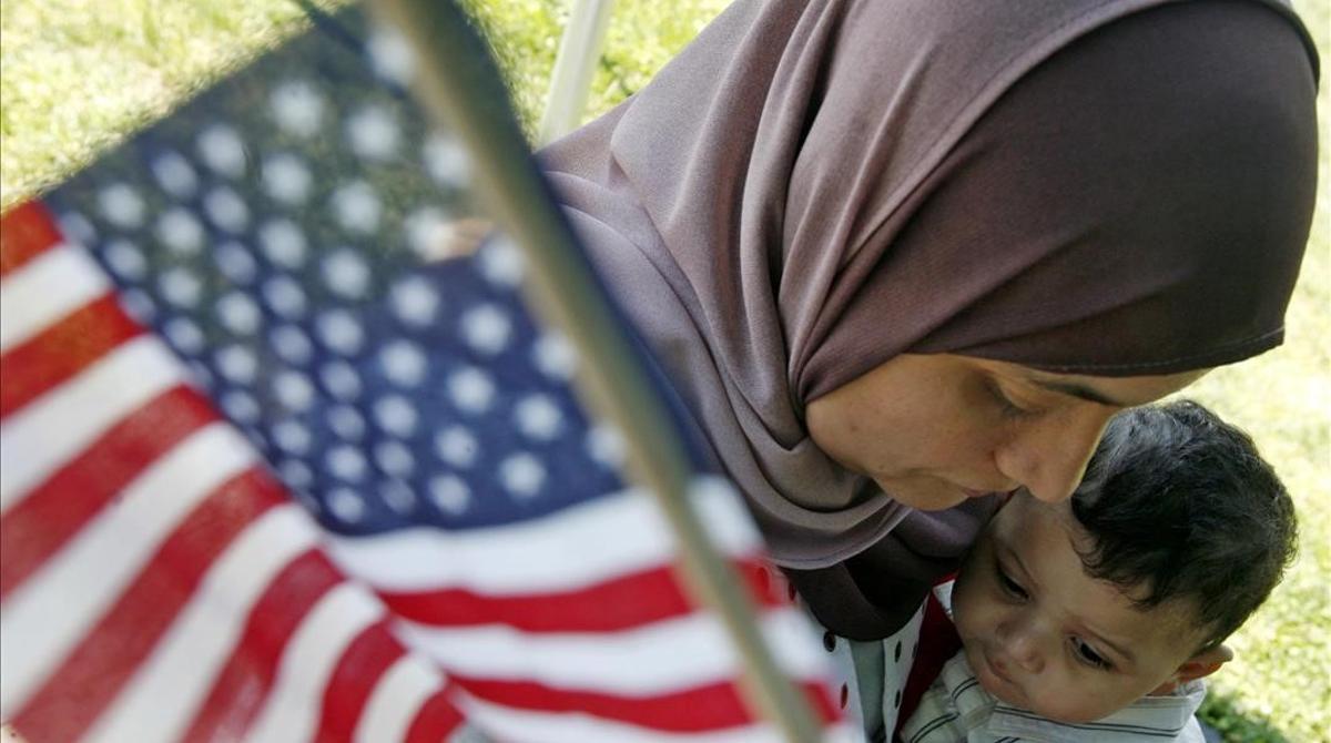 Una mujer marroquí sostiene una bandera de EEUU.