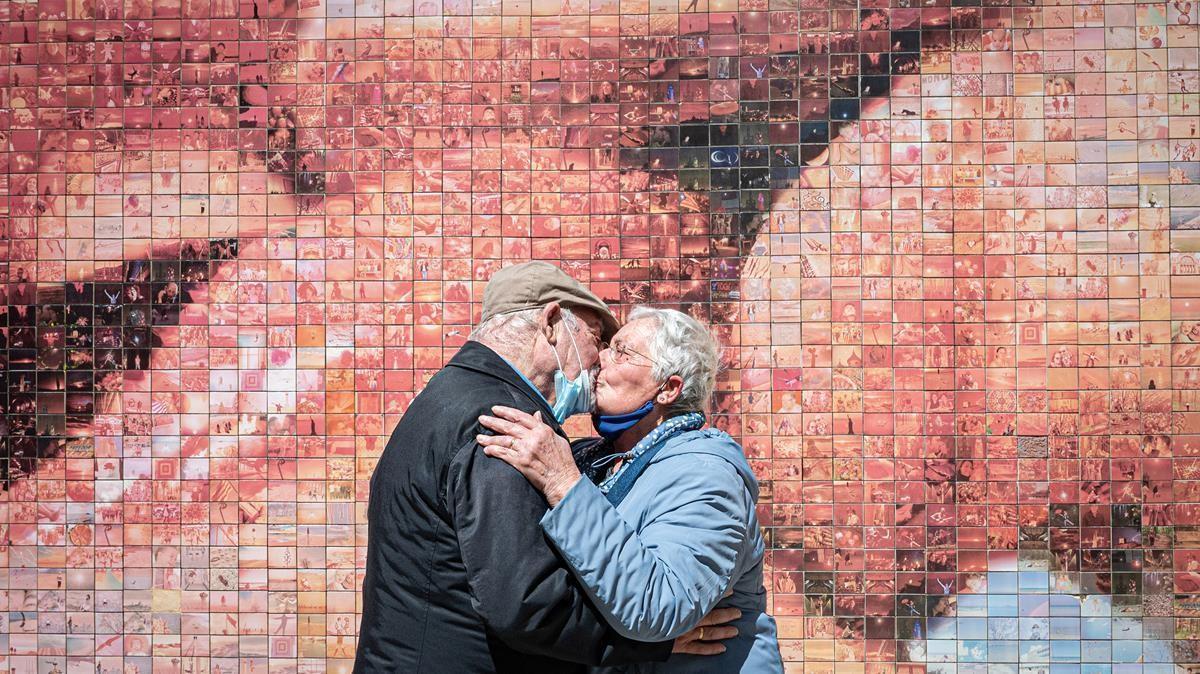 Un matrimonio de Barcelona se besa ante el mural de Joan Fontcuberta dedicado al beso.