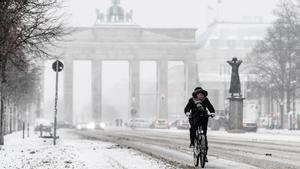 Un ciclista circula ante la puerta de Brandenburgo de Berlín durante la nevada del pasado día 8.