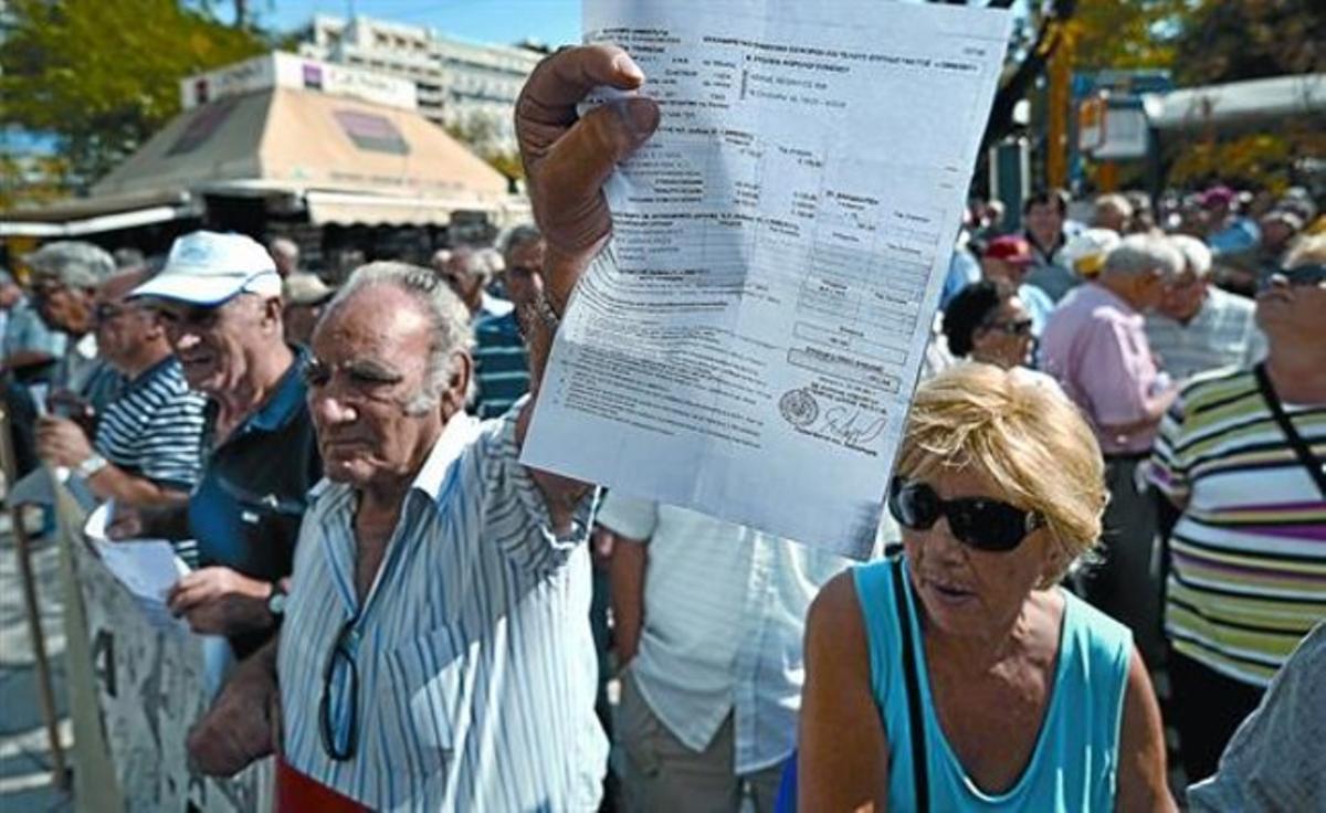 Un pensionista griego muestra el recibo de un impuesto durante una manifestación ante el Ministerio de Finanzas en Atenas.