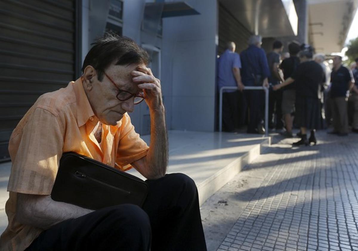 Giorgos, un pensionista de 77 años de Atenas, espera fuera del Banco Nacional de Grecia.