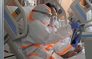 Un paciente del Hospital Sant Joan de Déu, de Palma, habla, por videollamada, con su familia, ayudado por una enfermera.