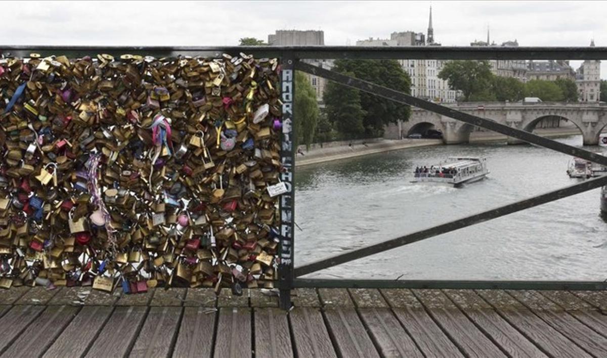 Barandillas del puente de las Artes, en París. La de la izquierda aún mantiene centenares de candados, mientras que la de la derecha ya ha sido vaciada por las autoridades de París.