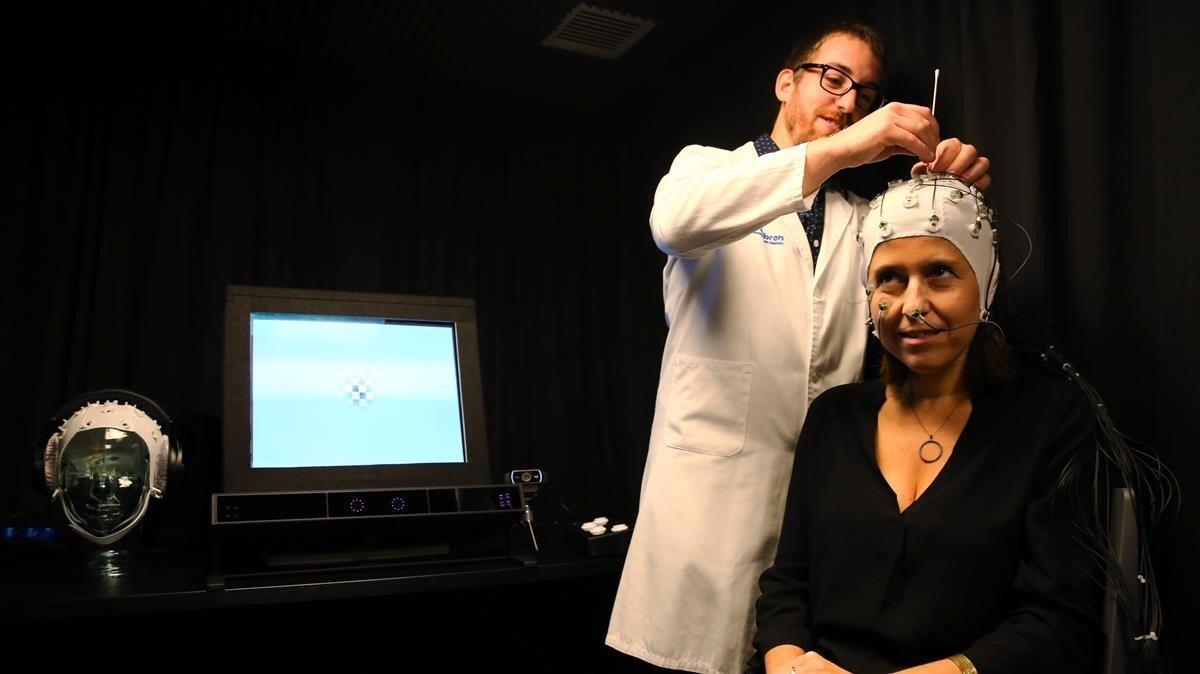 Un médico del Migraine Adaptive Brain Center coloca un gorro de encefalografía a una paciente, este jueves.