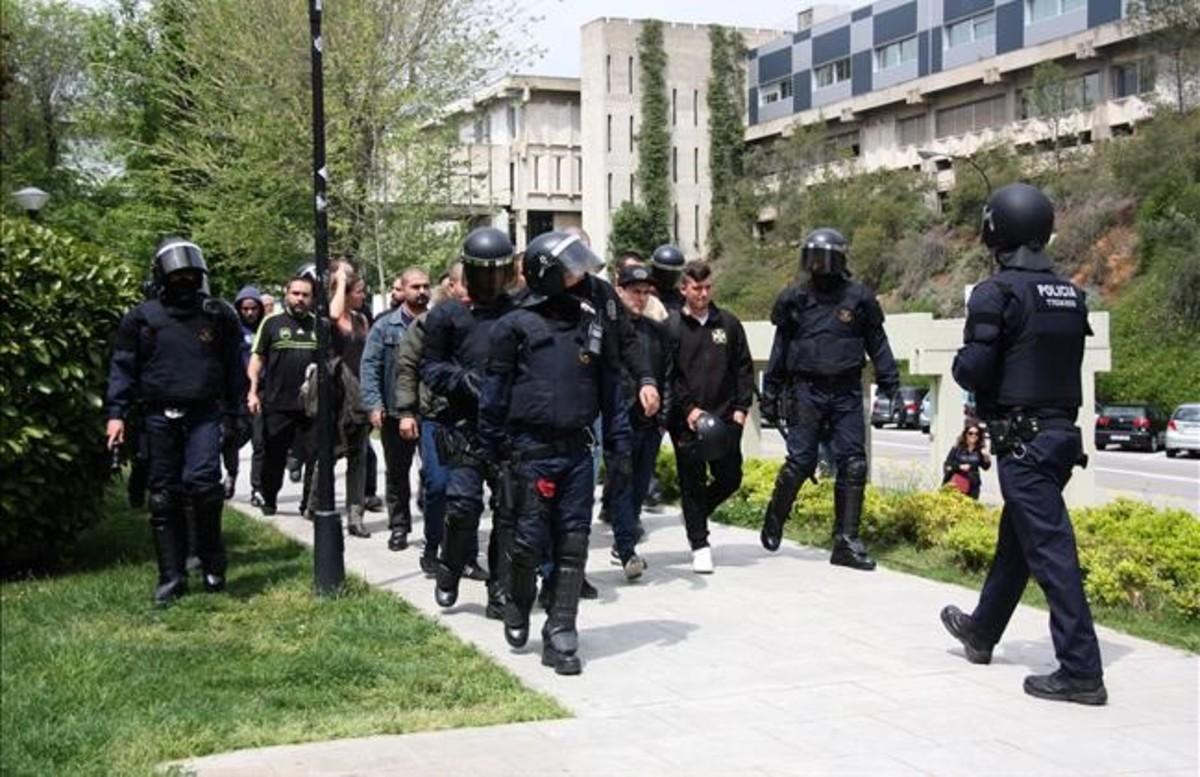 Los agentes se llevan a los neonazis al exterior de la UAB.