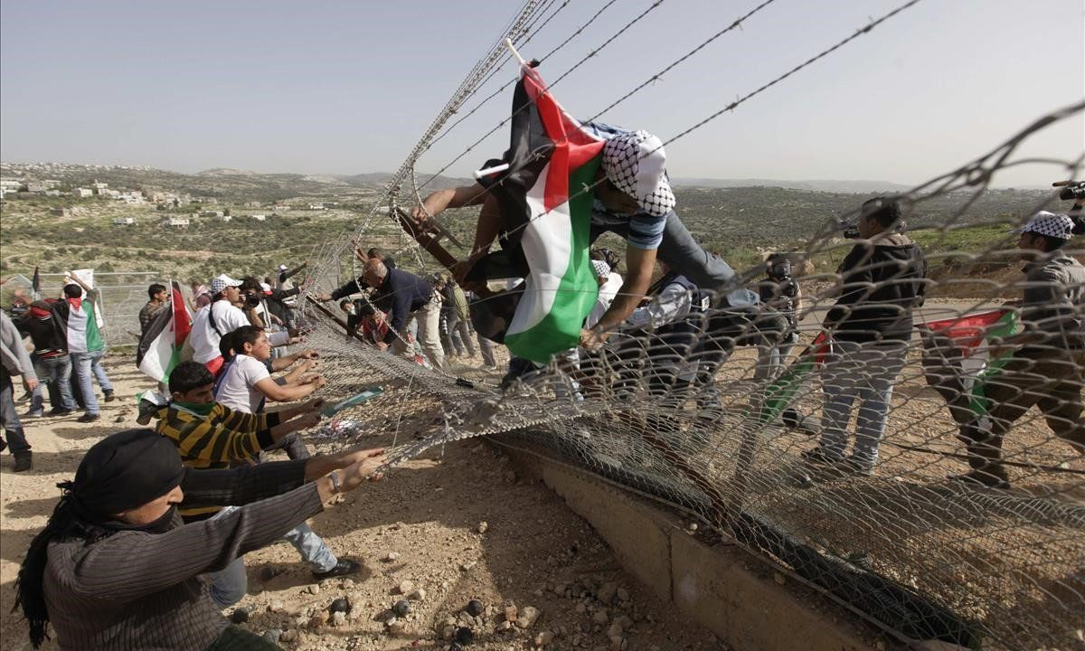 Manifestantes palestinos tratan de derribar una sección de la controvertida barrera israelí durante una protesta en la aldea de Bilin, cerca de Ramala, en Cisjordania.