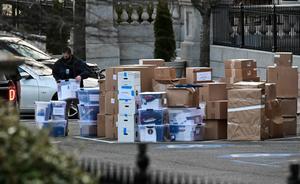 Un trabajador lleva una caja para ser transportada, en el exterior de la Casa Blanca.