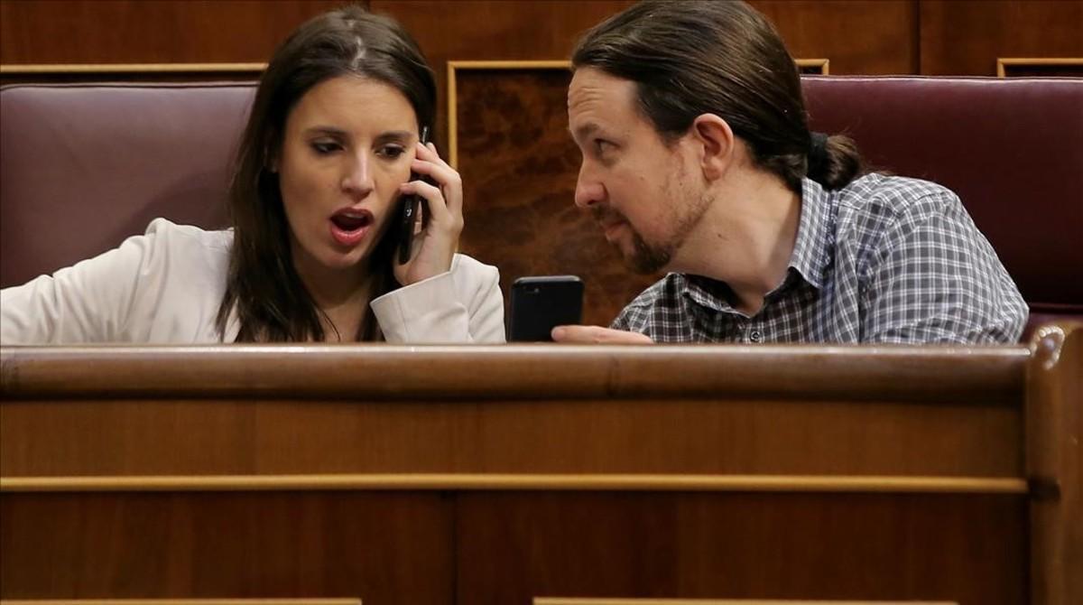 Pablo Iglesias muestra el móvil a Irene Montero durante el pleno en el Congreso.