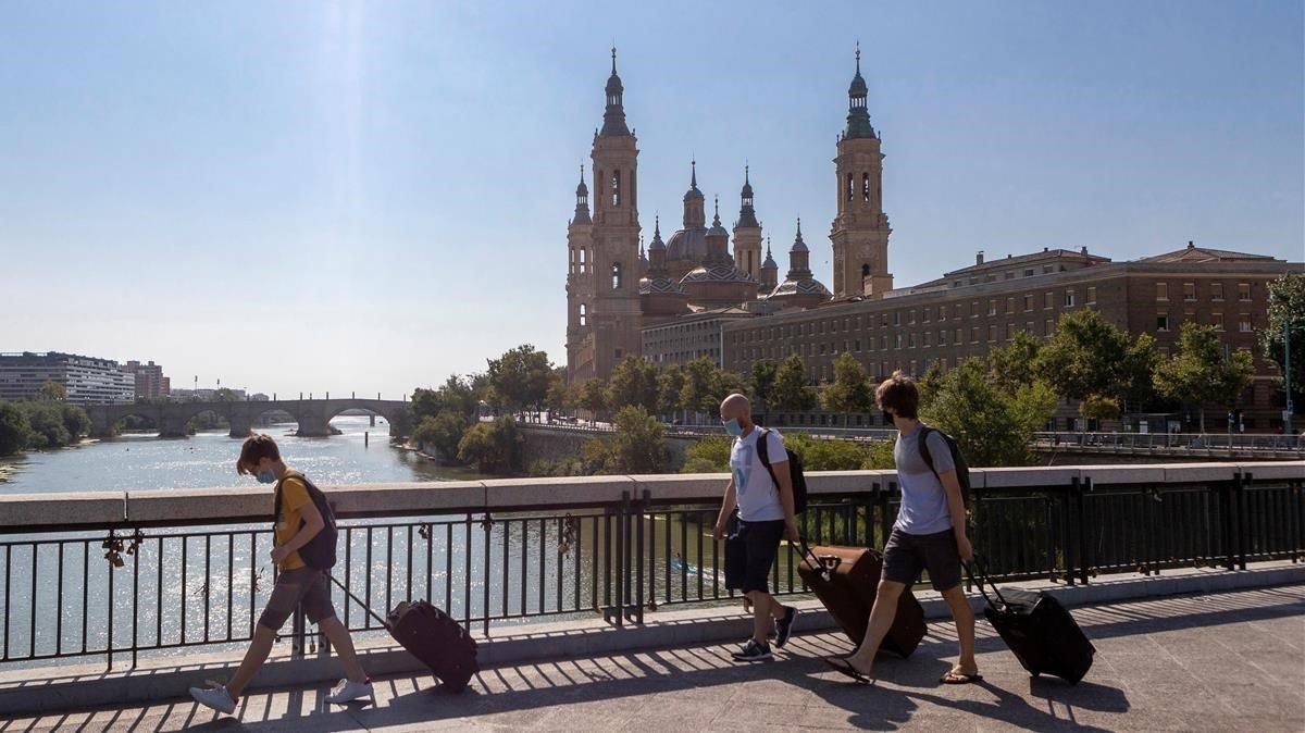 Personas con maletas cruzan el Puente de Santiago de Zaragoza, el pasado día 15.