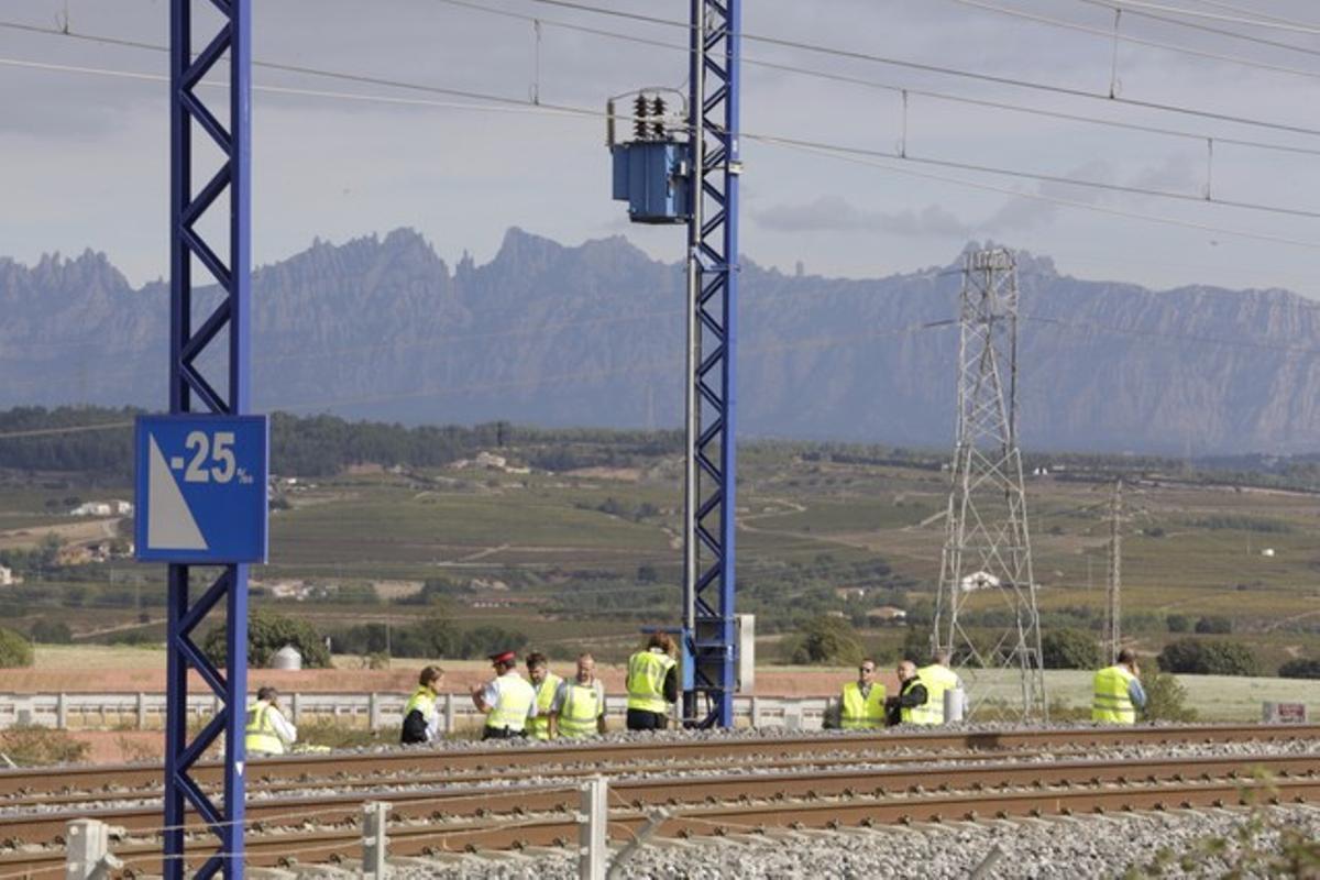Mossos y operarios inspeccionan la caja donde se ha producido el intento de robo de cable en la línea del AVE.