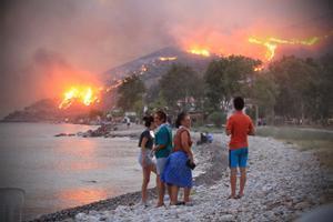 Gente en la playa observa la expansión de las llamas en la ciudad costera de Oren, en la región turca de Mugla.