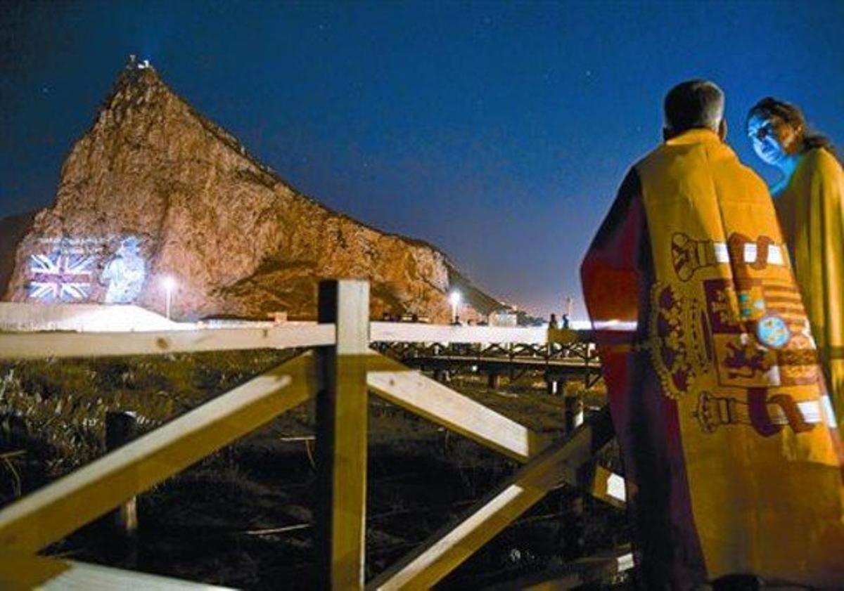 Una parella mira des de la Línea de la Concepción la projecció de la imatge d'Isabel II al Penyal, dimarts.