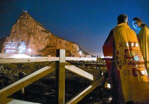 Una pareja mira desde la Línea de la Concepción la proyección de la imagen de Isabel II en el Peñón, en junio del 2012, cuando las autoridades de Gibraltar celebraron el 60º aniversario del ascenso al trono de la reina.