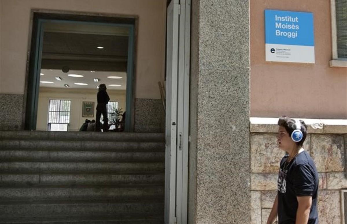 Un joven pasa por delante del instituto público Moisès Broggi, en el distrito de Sant Martí de Barcelona.