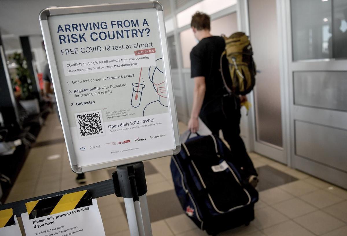 Un cartel informa de los test de coronavirus en el aeropuerto de Schönefeld, en Berlín.
