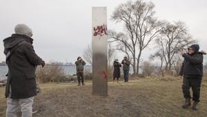 Varios habitantes de Toronto fotografían el misterioso monolito, que ya ha sido vandalizado con grafitis.