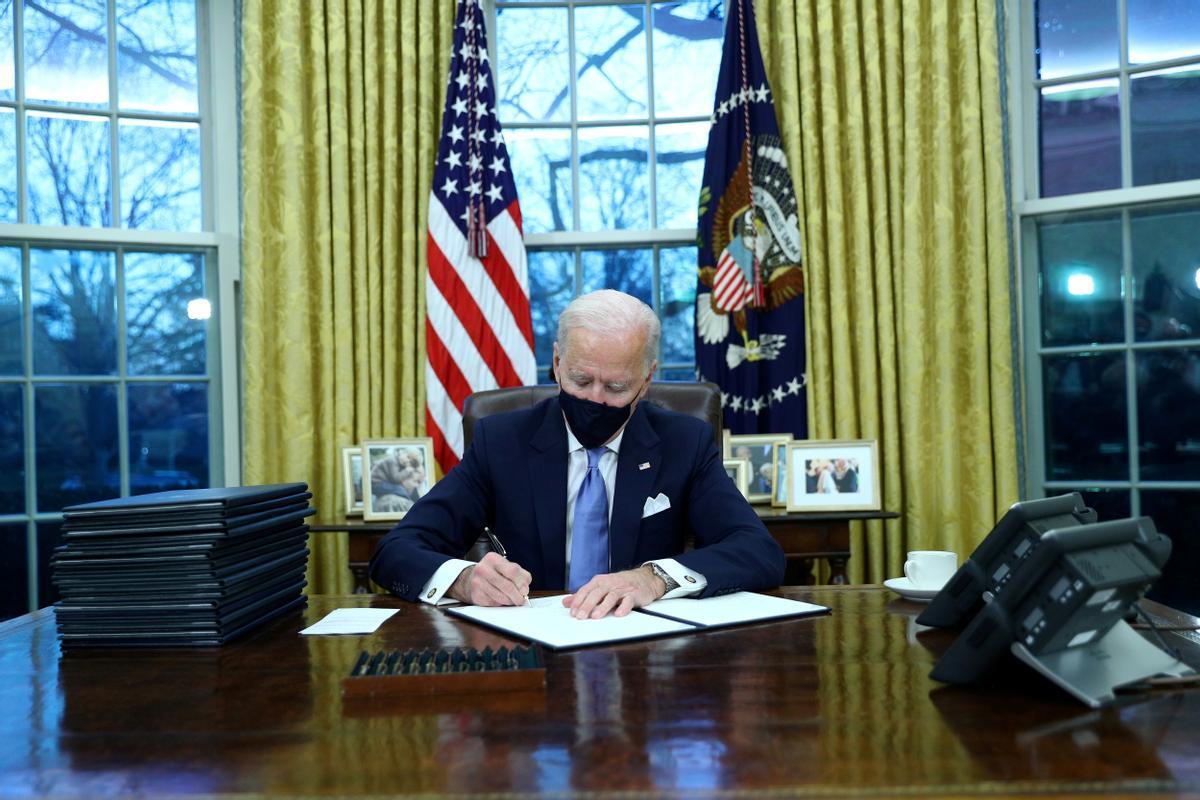 Biden, en el Despacho Oval, firma sus primeras órdenes.