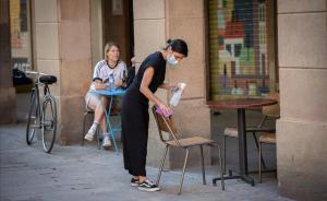Una camarera desinfecta mesas y sillas en la terraza de un bar de Barcelona.