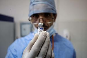 Imagen de archivo de un sanitario sosteniendo un vial de la vacuna Sputnik V.