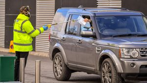 Un miembro de seguridad de un centro donde se realizan tests de coronavirus en Bristol (Reino Unido) coge la documentación de una de las personas, este lunes.