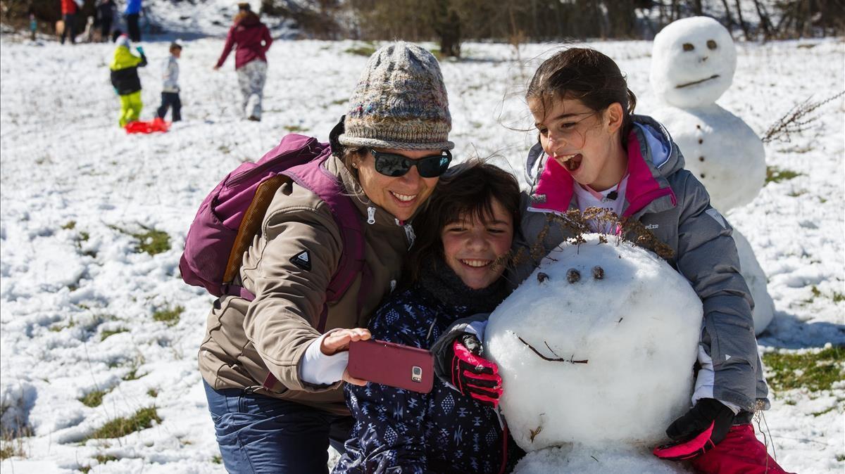 Una mujer realiza un 'selfie' a cuatro tras dar por terminada la labor de levantar un muñeco de nieve, este, sin zanahoria.