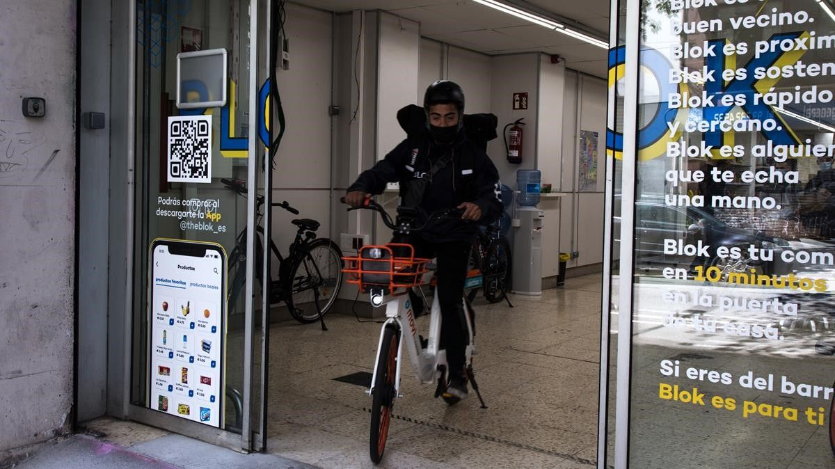 Un empleado sale para hacer un reparto de productos de alimentación desde el almacén de Blok en la calle de Sicília, 159.