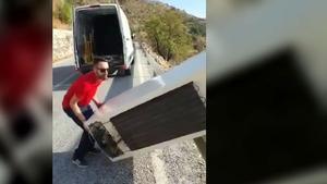 Un hombre tira una nevera en el monte.