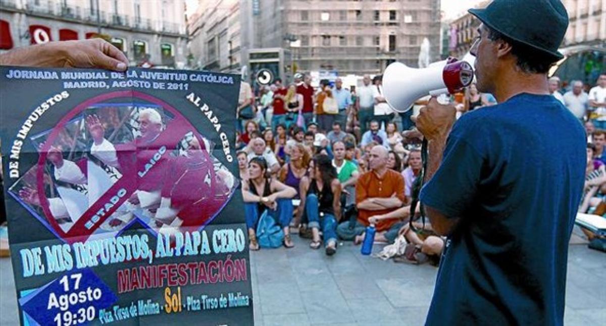Un cartel crítico con la visita del Papa presidía ayer una asamblea de indignados celebrada en la Puerta del Sol.