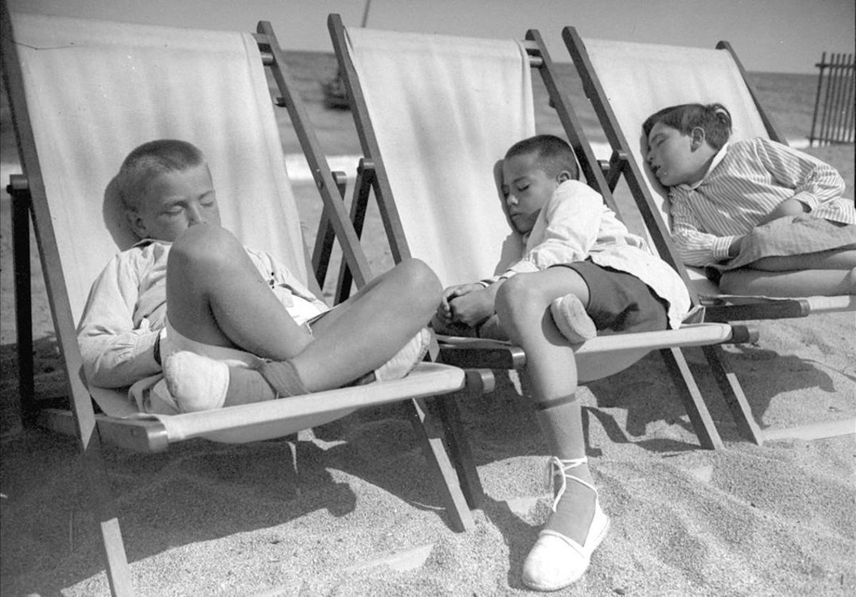 Alumnos de la Escola del Mar durmiendo la siesta sobre unas hamacas en la playa de la Barceloneta, que era utilizada como patio del colegio.